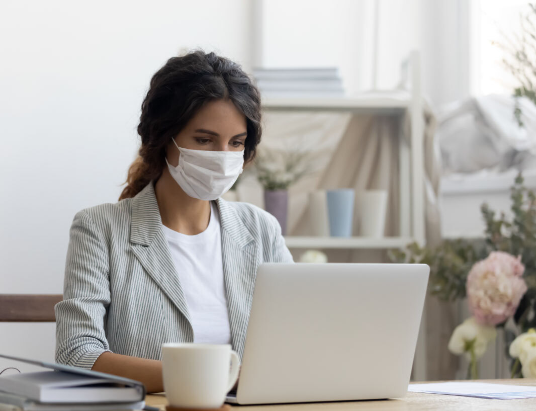 A woman wearing a non-surgical mask, safely translating at her computer.